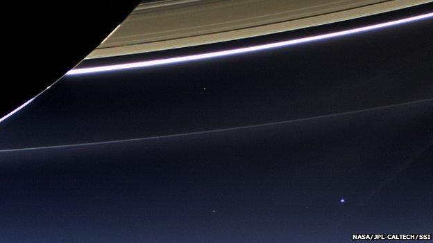 لأرض والقمر يبدوان كنقطتين زرقاوين في أسفل يمين الصورة